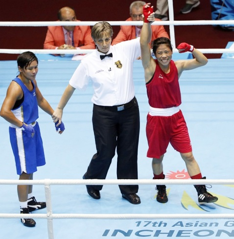 Referee Hammadi Sidi Yakoub declares India's Hmangte the winner of the women's fly (48-51kg) boxing match final against Kazakhstan's Shekerbekova at the Seonhak Gymnasium during the 2014 Asian Games in Incheon