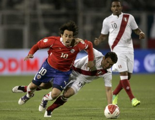 Chile's Jorge Valdivia, left, is tackled by Peru's Renzo Revoredo, center, during a 2014 World Cup qualifying soccer game in Santiago, Chile, Tuesday, Oct. 11, 2011. (AP Photo/Aliosha Marquez)