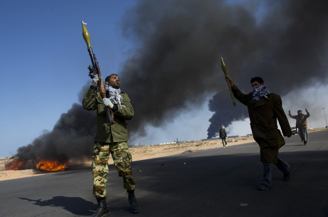 Opposition troops burn tires to use as cover during heavy fighting, shelling, and airstrikes near the main checkpoint near the refinery in Ras Lanuf as rebel troops pull back from Ras Lanuf, in Eastern Libya, March 11, 2011. Qaddafi's troops have been advancing East, and re-taking territory that had previously fallen to the rebels, as they batter the rebels with artillery and air strikes. (Credit: Lynsey Addario for The New York Times)