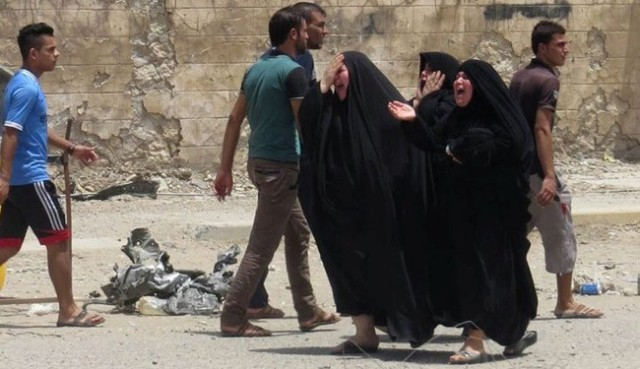 Women react at the site of a car bomb attack in the town of Tuz Khurmato, north of the capital Baghdad, June 9, 2014.