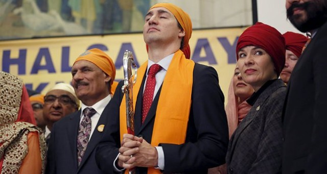 Canada's Prime Minister Justin Trudeau (C) holds a ceremonial sword that was presented to him while taking part in a Vaisakhi celebration on Parliament Hill in Ottawa, Canada, April 11, 2016. REUTERS/Chris Wattie