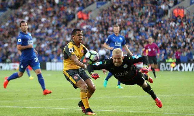 Kasper Schmeichel clears the ball away ahead of Alexis Sanchez.