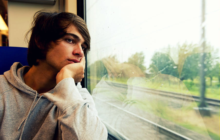 Bored young man, staring out the train window on a rainy, grey and dull day