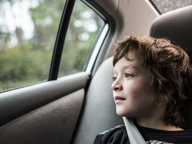 little-boy-with-seatbelt-looking-out-car-window