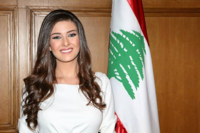 A Christian Lebanese model poses with the national flag.