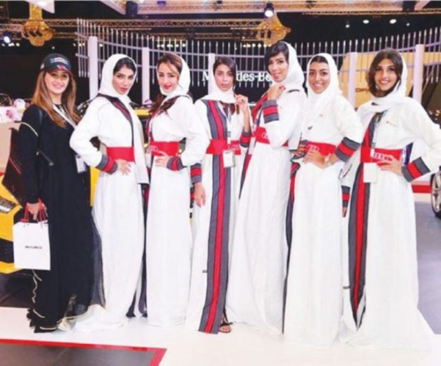 Models posing in front of a car at a luxury auto show in Jeddah, Saudi Arabia