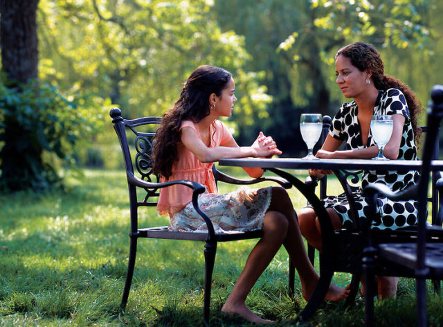 A mother and daughter talk while sitting at a table with lemonade outside