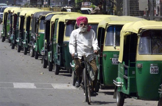 A CYCLIST PASSES BY A QUEUE OF RICKSHAWS WAITING TO FILL THEIR TANKS AT A COMPRESSED NATURAL GAS STATION IN NEW DELHI. A cyclist passes by a queue of auto-rickshaws waiting to fill their tanks at station selling compressed natural gas in New Delhi April 2, 2001. Commuters in the Indian capital were stranded for a second day running on Monday as thousands of buses and taxis went off the roads under a court order to switch to the cleaner fuel. Some 15,000 private and state-run buses and thousands of taxis and three-wheelers had been ordered by the Supreme Court to change to compressed natural gas from diesel by April 1 in a drive to clean the capital's dirty air.