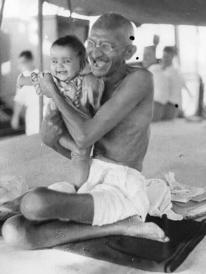 Mahatma Gandhi being playful with a child