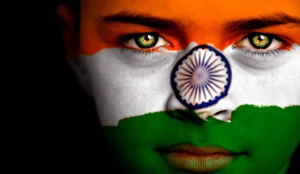 Portrait of a boy with the flag of India painted on his face.