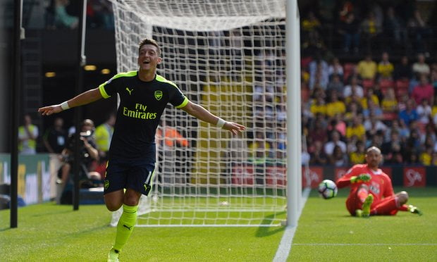 Mesut Ozil wheels away in celebration after scoring against Watford.