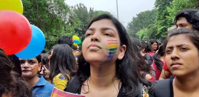 Girl proudly showing off the pride flag painted on her face