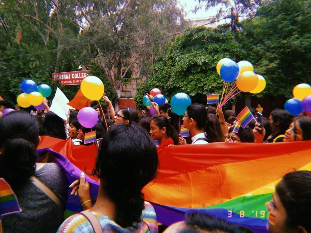 "A pride parade passing underneath a sign saying, ""Hansraj Hostel"""