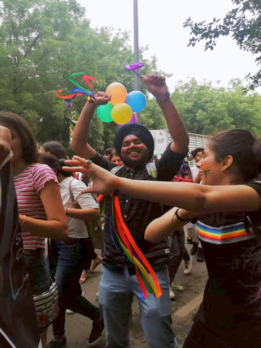 A sikh man dancing at an LGBT pride parade, with ribbons tied to his wrists