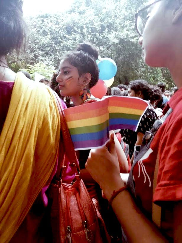 a girl at hansraj pride standing, showing off her face paint