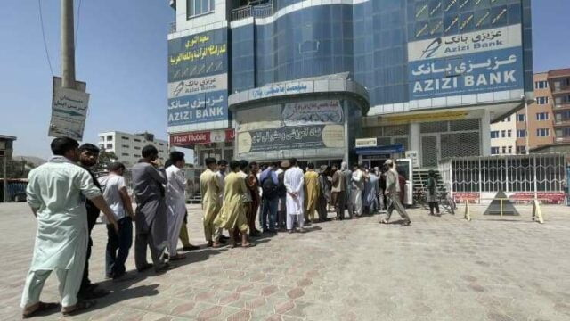 """Afghan people line up outside AZIZI Bank to take out cash as the Bank suffers amid money crises in Kabul, Afghanistan, on August 15, 2021. Haroon Sabawoon 