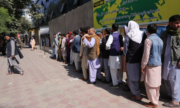 People wait outside a bank to withdraw cash on 16th August after the Taliban's takeover of Kabul. Queues can stretch for hundreds of metres