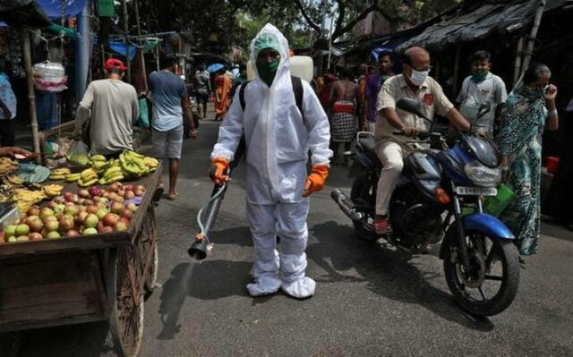 A municipal worker sprays disinfectant to sanitise a street amidst the spread of the coronavirus pandemic in Kolkata