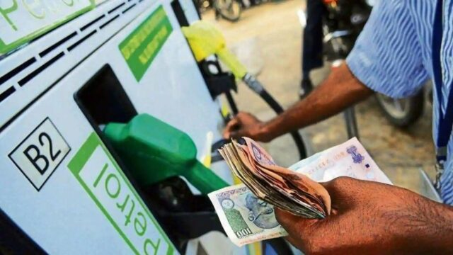 Fuel prices hiking in India. A worker in a petrol pump in Delhi counting money.